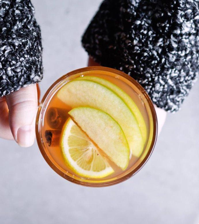 Чашка теплого глинтвейна с яблоком и лимоном
