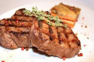 Мясо на тарелке и перец розовый горошком